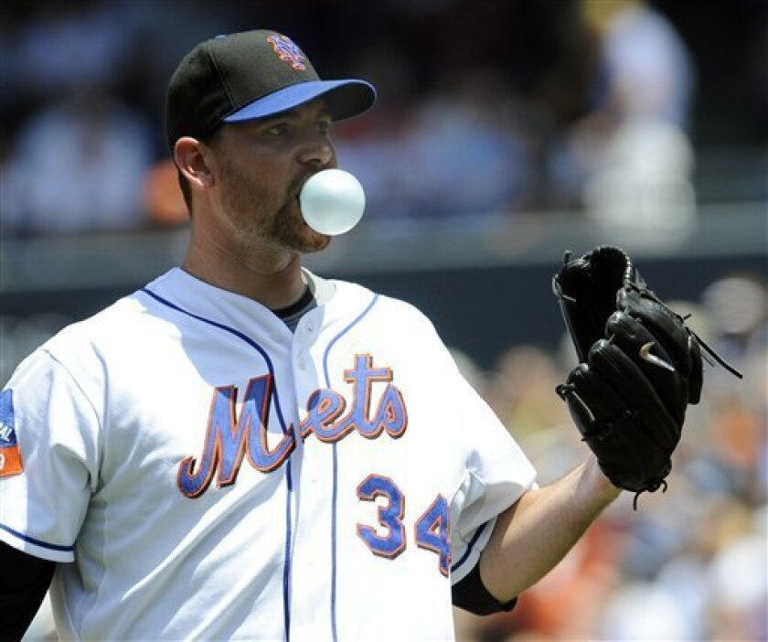 New York Mets pitcher Mike Pelfrey blows a bubble as he waits for the throw back from the catcher while pitching in the first inning of the baseball game against the Cincinnati Reds at Citi Field in New York, Sunday, July 12, 2009. (AP Photo/Paul J. Bereswill)
