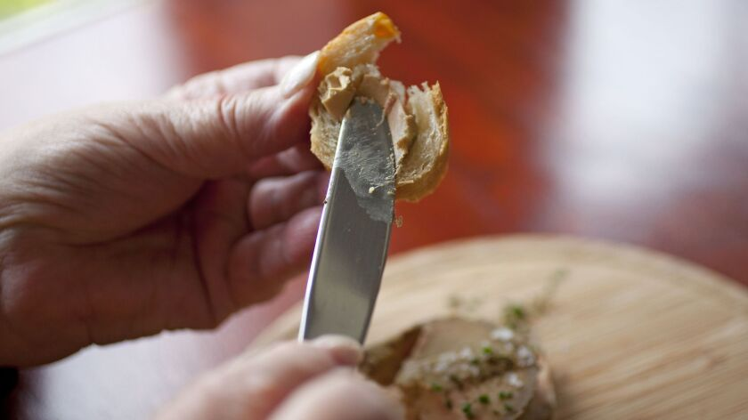 FILE - In t his July 17, 2012, file photo, a diner spreads foie gras, made from the liver of ducks o