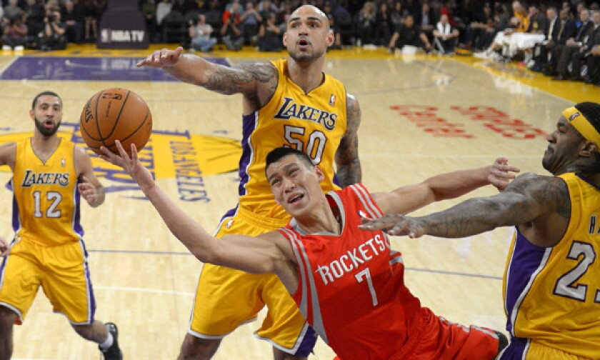 Houston Rockets guard Jeremy Lin, bottom, puts up a shot between Lakers teammates Kendall Marshall, left, Robert Sacre, center, and Jordan Hill during the Lakers' 134-108 loss on Feb. 19.