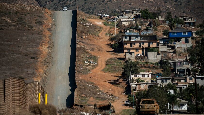 TIJUANA, B.C., MEX - FEBRUARY 01: A vehicle sits at the top of a hill in the alley between border wa