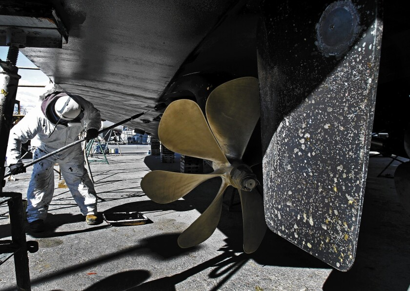 A worker paints the hull of a yacht at Marina del Rey Harbor, where officials are considering a plan that would require boaters to stop using copper paint.
