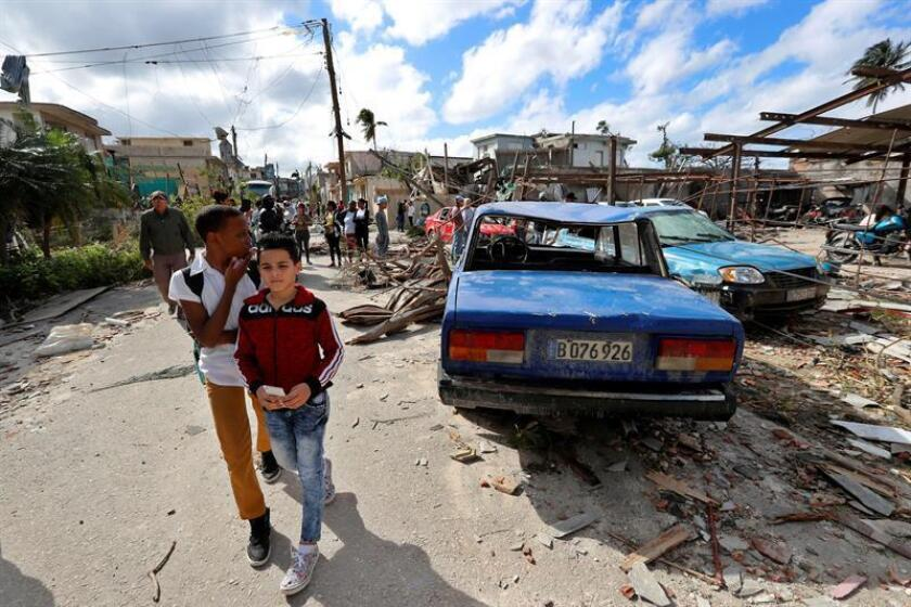 Two children walk pas rubble and destroyed cars at the municipality of Luyano, in Havana, Cuba, 28 January 2019. A dozen out of the 172 wounded in a tronado that hit Havana last night remain in critical state. EPA- EFE/ Ernesto Mastrascusa