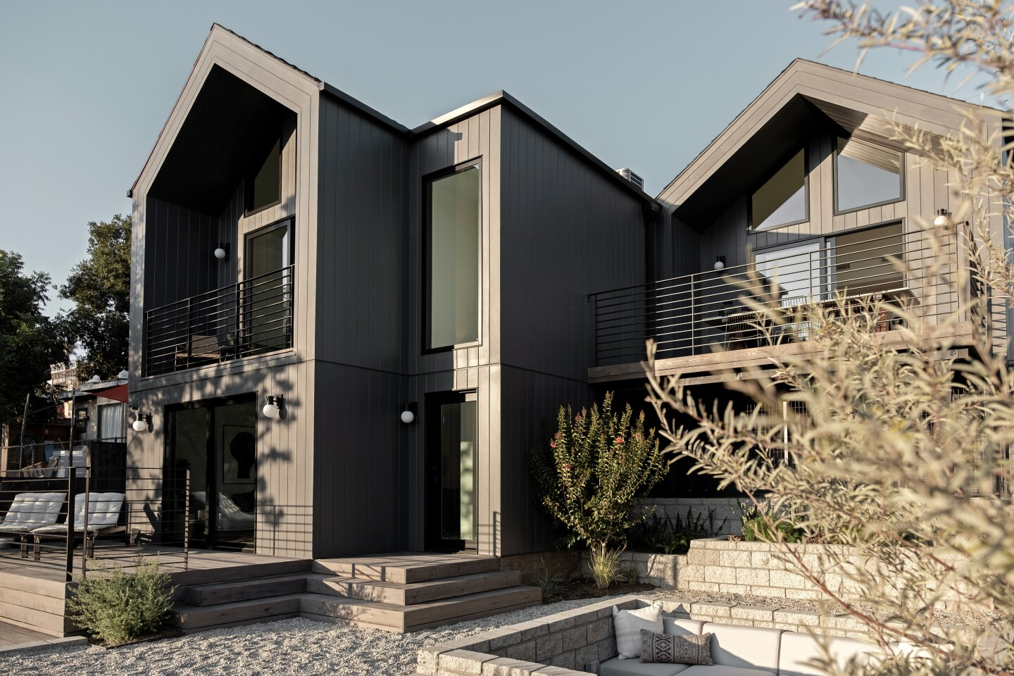 Listed for $1.295 million, the subdued Eagle Rock residence was completed this year and retains only the original foundation of a former bungalow. The bright, austere interior of the newly built home was inspired by Scandinavian design, which emphasizes clean lines and functional living spaces. Built-in booth seating in the kitchen matches the custom cabinetry and light oak floors. A dining terrace sits off the kitchen area. The backyard unfolds layers with tiers of various planters, decks and a sunken conversation/fire pit.