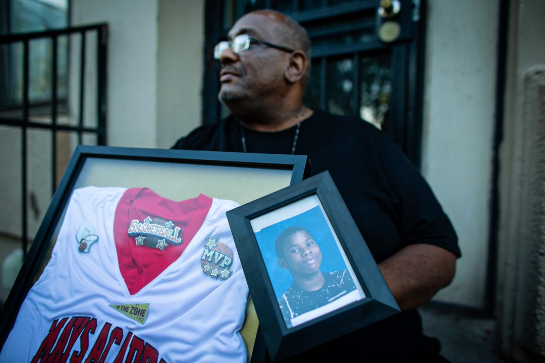 Donald Williams sits on the stoop of his home holding a photo and basketball jersey of his late son Deon Williams
