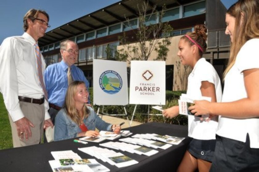 Head of School Kevin Yaley (left) and San Diego River Park Foundation Trustee Jim Dawe observe as Marly Isler signs her nature guide booklets for Class of 2017 Francis Parker School students Katherine Dews and Marly's sister Megan Isler. Courtesy