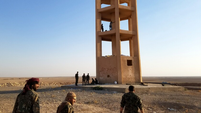 U.S.-backed Syrian opposition fighters standing watch against Islamic State atop a water tower in no