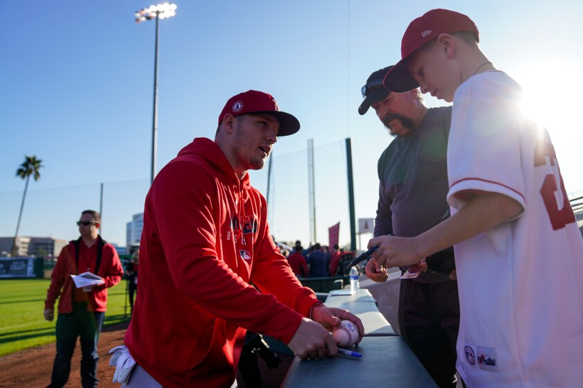 The Angels' Mike Trout signs a ball for fans at Tempe Diablo Stadium in Tempe, Ariz.