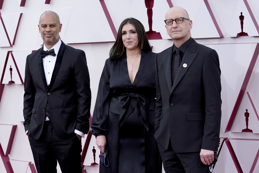 Jesse Collins Stacey Sher and Steven Soderbergh, in black formal wear, pose for a picture.