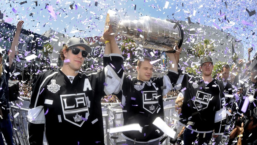 Kings teammates (from left to right) Anze Kopitar, Dustin Brown and Jonathan Quick celebrate the team's Stanley Cup victory in front of Staples Center on June 16.