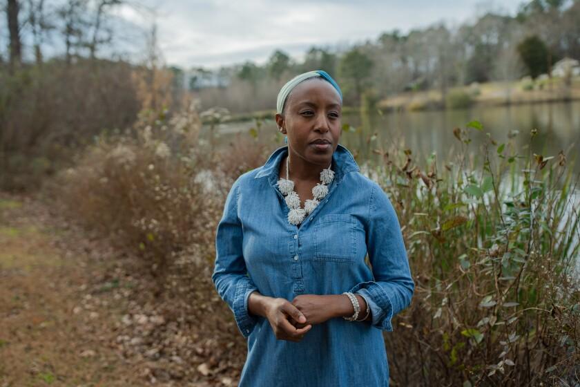 Dana Evans, 43, stands by a lake near her home in Stockbridge, Ga.