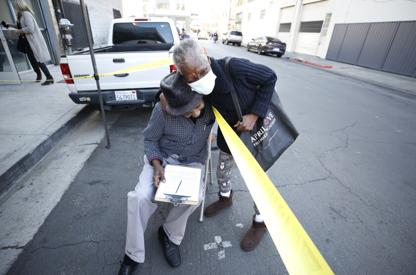 Two people on a city street, one in a mask, hug over a string of yellow tape.