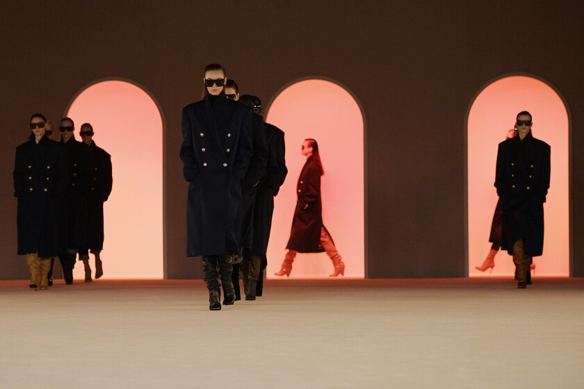 Models in long Navy-style double-breasted coats and dark sunglasses.
