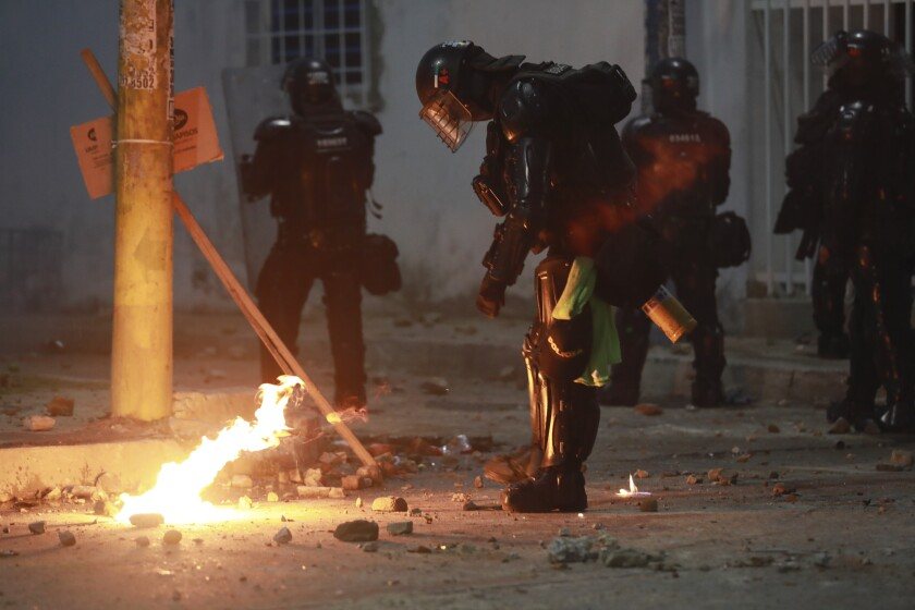 Riot police putting out petrol bomb