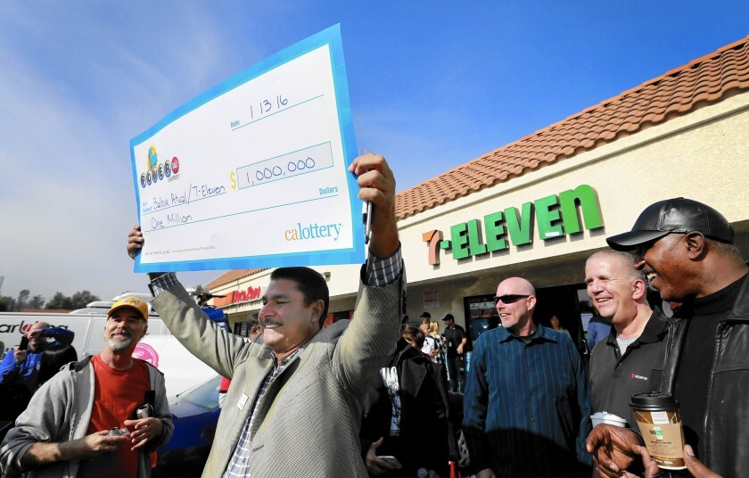 Balbir Atwal, owner of the 7-Eleven store in Chino Hills that sold a winning Powerball ticket, holds up an oversized prop check for $1 million, the business' take for selling one of the three tickets that won the $1.5-billion jackpot.