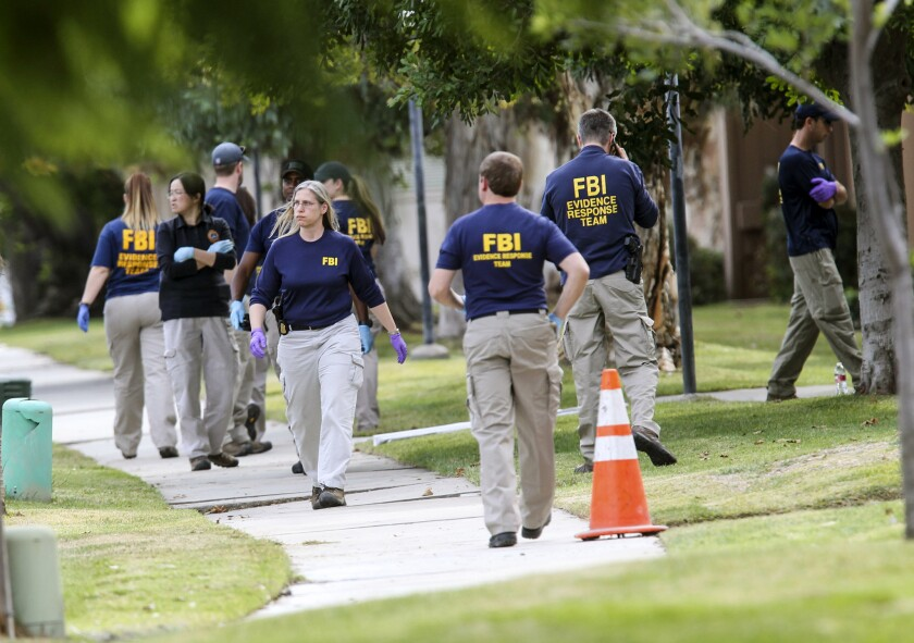 FBI agents search outside a home in connection to the shootings in San Bernardino on Dec. 3 in Redlands.