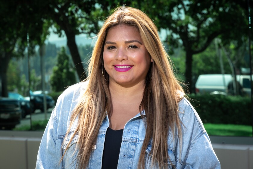 Geena Aguilar pictured from the chest up, in a denim jacket and smiling at the camera