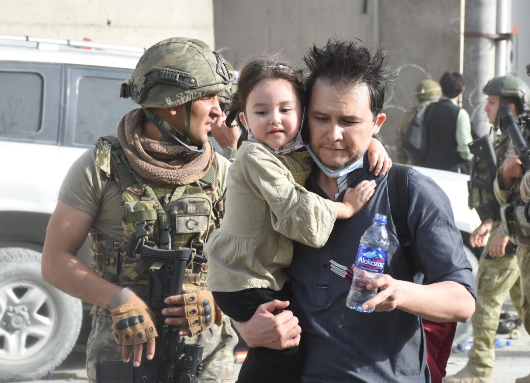 Turkish soldiers help a father as people waiting for evacuation at Hamid Karzai International Airport in Kabul, Afghanistan.
