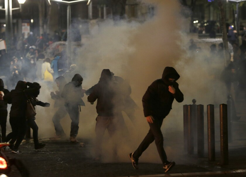 Demonstrators run through clouds of teargas during clashes with police in Marseille, southern France, on Saturday during protests against what they claim were dilapidated residential buildings that collapsed Monday, Nov. 5, killing eight people.