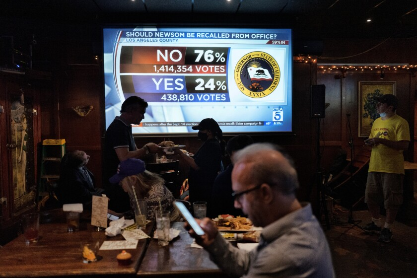 A big screen shows vote numbers while people eat in a restaurant..