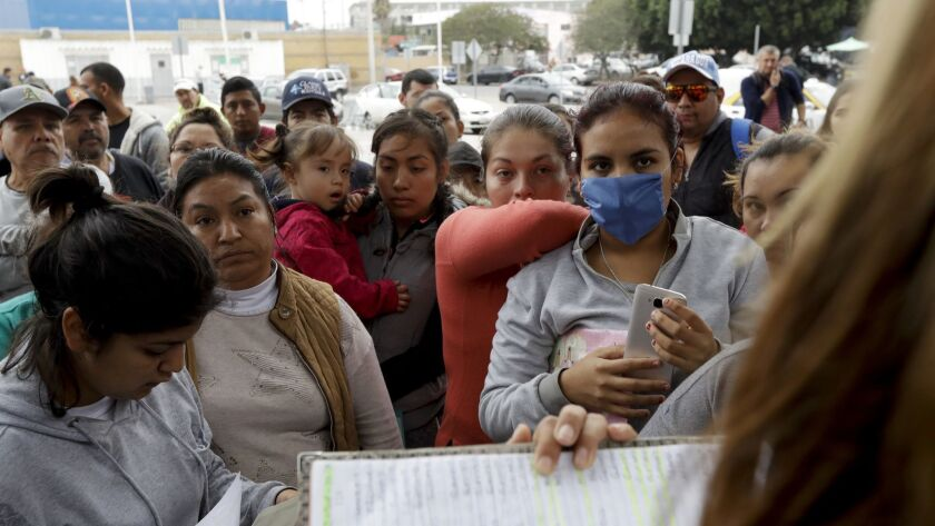 In this Oct. 23, 2018, photo, women in Tijuana look on as numbers and names are called to cross the border and request asylum in the United States.