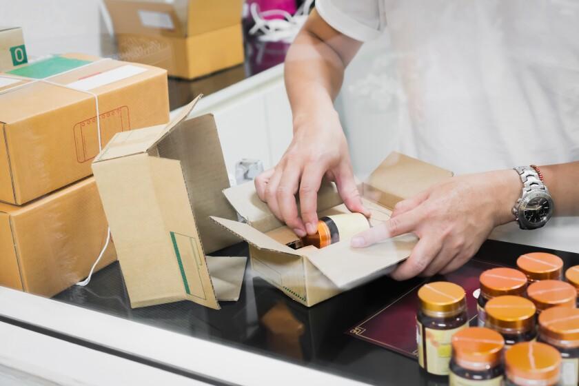 Los empleados embalan un paquete en el envío al cliente. Pedidos en línea para la comodidad de los clientes.