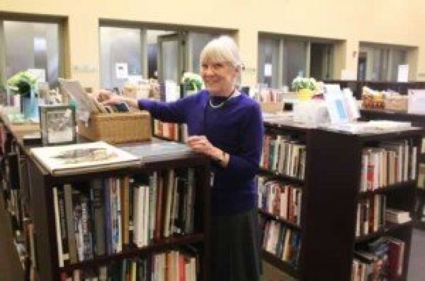 Librarian Catherine Greene sifts through the books for sale from the Friends of La Jolla Library at the Riford branch. Ashley Mackin