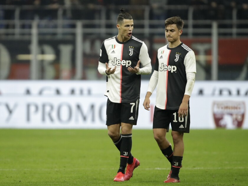 FILE - In this Feb. 13, 2020 file photo, Juventus' Cristiano Ronaldo, left, speaks with Juventus' Paulo Dybala at the end of an Italian Cup soccer match between AC Milan and Juventus at the San Siro stadium, in Milan, Italy. With Inter, Juventus and Milan -- plus Napoli -- all in action when Italian soccer restarts with the Italian Cup semifinals this week, the effects of the pandemic will still be fresh in the minds of players, coaches and club executives. Without fans inside the stadiums, the second-leg matches begin with Juventus hosting Milan on Friday, June 12, 2020, following a 1-1 first leg. (AP Photo/Luca Bruno, file)