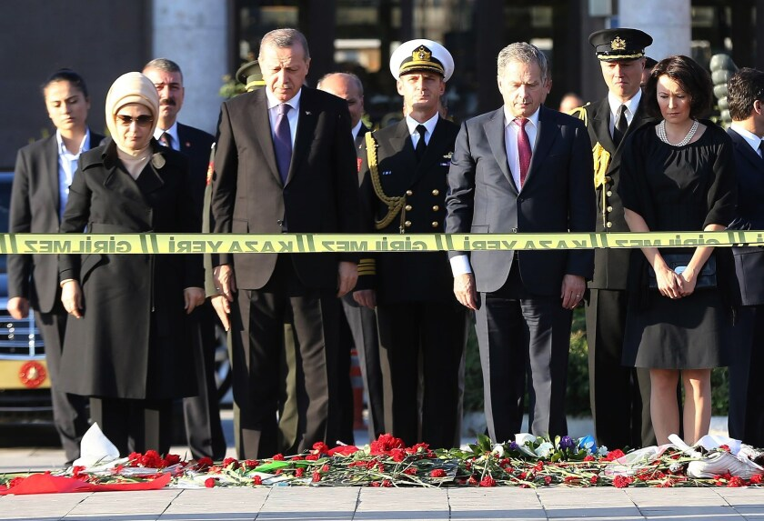 Turkish President Recep Tayyip Erdogan, second from left, and Finish President Sauli Niinisto attend a wreath-laying ceremony at the site of the twin bombings in Ankara.