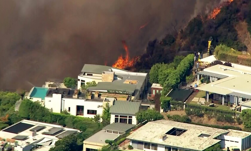 Brush fire in Pacific Palisades threatens homes as residents flee