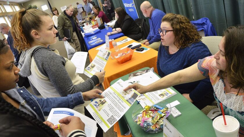 Kim Wesley, area supervisor for ResCare Residential Services, right, and Rhonda Purvis, a staff member, talk with job seekers at a job fair in Marion, Ind.