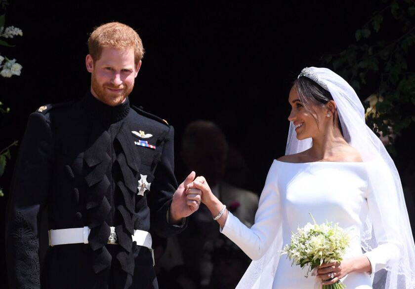 The new Duke and Duchess of Sussex hold hands as they exit St. George's Chapel at Windsor Castle after their royal wedding ceremony on Saturday.