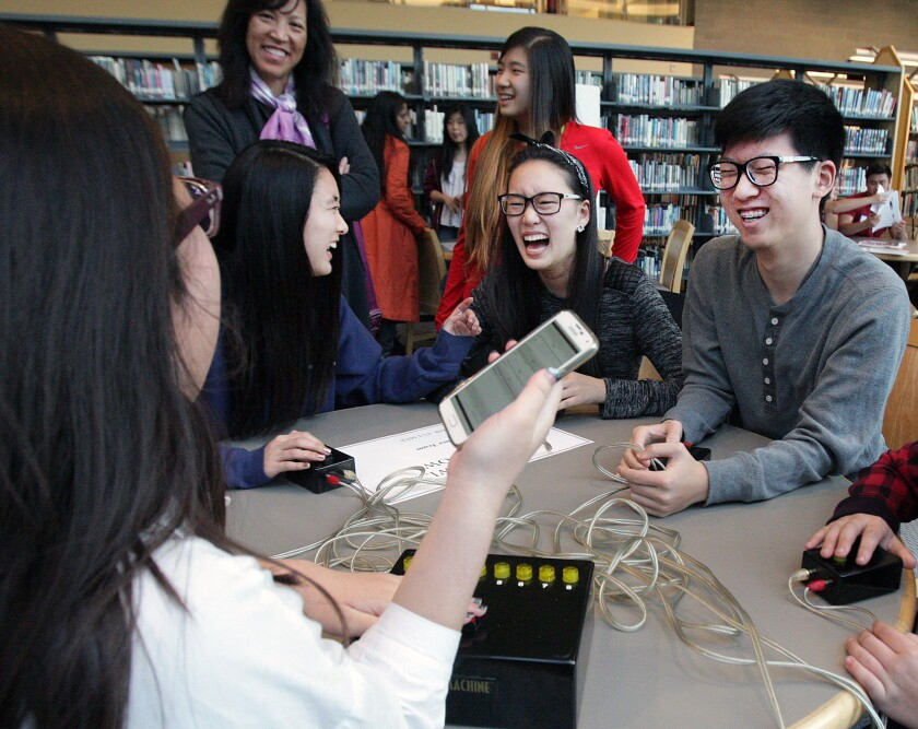 La Cañada High School students Sharyse Watanabe, 18, Hannah Chong, 18, and Daniel Oh, 16, laugh as they answer Science Bowl and Ocean Bowl questions at the annual Showcase Science event at La Cañada High School on Thursday, Feb. 4, 2016.