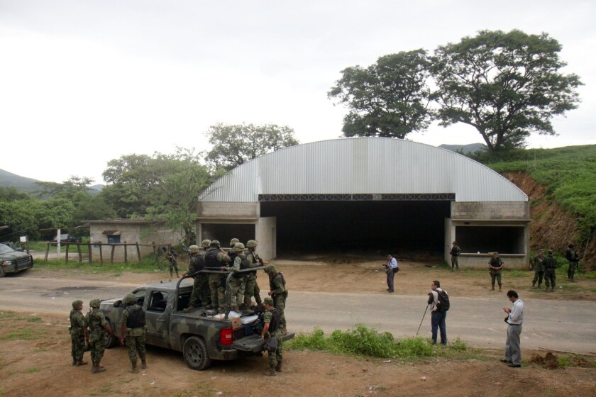 Mexican soldiers patrol the entrance to the Tlatlaya community where 22 people, alleged members of the Drug Cartel, were killed in a confrontation with soldiers of the Mexican Army. Military troops targeted by armed assailants who were guarding a warehouse returned fire June 30, 2014, killing 22 suspects.