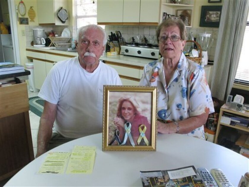 In this photo taken March 29, 2012, Carl and Jeanne Elliott sit in their kitchen with a photo of their 17-year-old daughter Lynn, who was murdered by David Alan Gore in Vero Beach, Fla. in 1983. David Alan Gore is scheduled to be executed Thursday, April 12, 2012 in Starke, Fla. (AP Photo/Brendan Farrington)