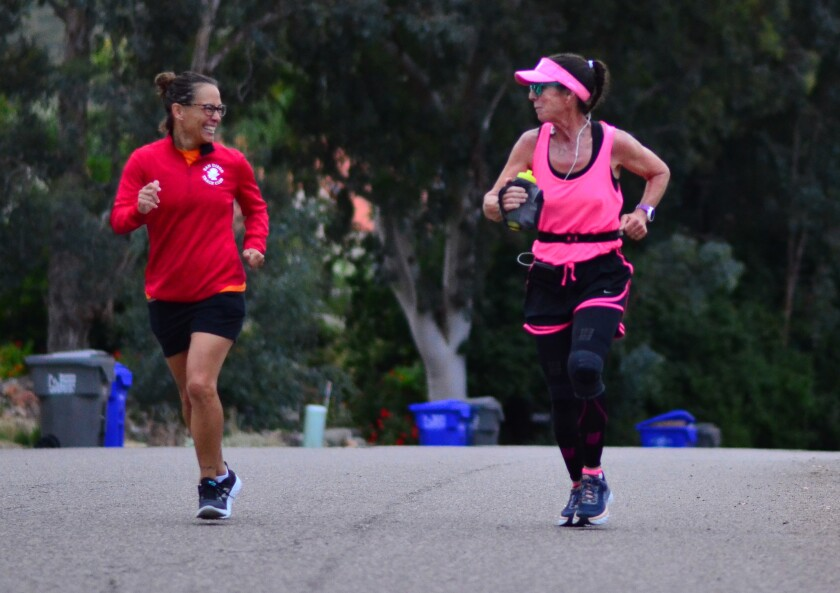 Kelly Van Zant Maine, right, running her own private marathon in Ramona, supported by friend Jamie Fryrear.