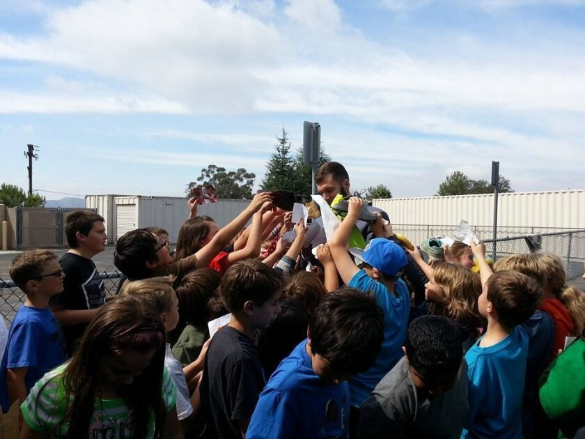 Ryan Lindley is mobbed by student autograph seekers.