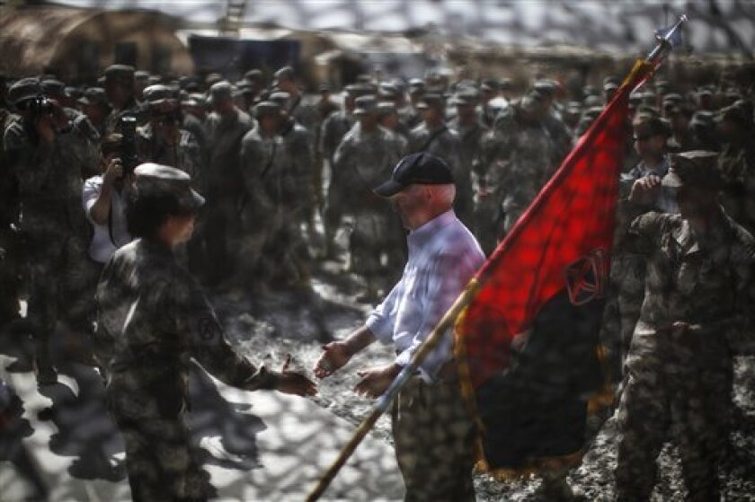 Defense Secretary Robert Gates is seen through camouflage netting as he greets US. Army soldiers at Forward Operating Base (FOB) Shank in Logar Province, Afghanistan, Monday, June 6, 2011. (AP Photo/Jason Reed, Pool)