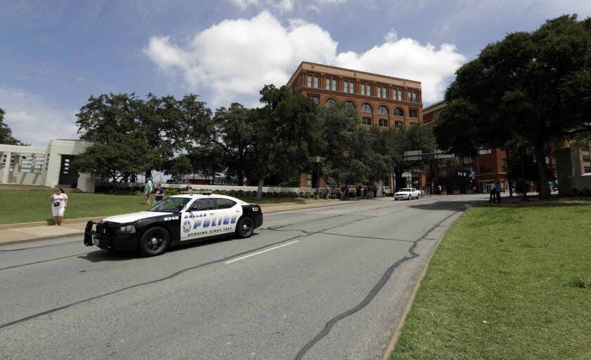 A Dallas patrol car passes Dealey Plaza in front of the Texas School Book Depository building, Saturday, July 9, 2016, in Dallas. After five police officers were killed in a shooting Thursday, a city forever haunted by the assassination of John F. Kennedy is trying to not let the worst America atta