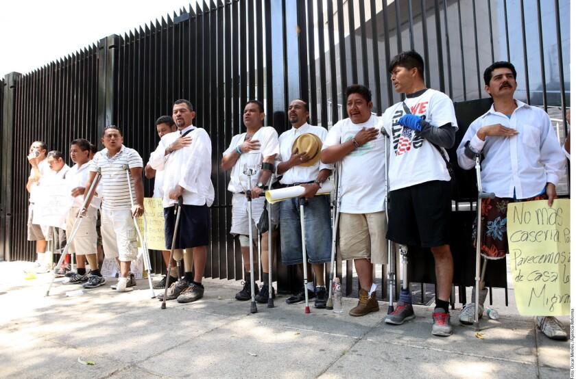 """Vestidos la mayoría con playeras blancas y shorts color caqui, 17 hondureños se colocaron en la reja del Senado mexicano con carteles en los que se lee: """"No más migrantes desaparecidos, secuestrados y mutilados"""" y """"No somos terroristas amamos la paz""""."""