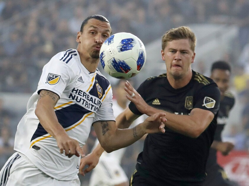 Los Angeles Football Club defender Walker Zimmerman, right, battles Galaxy forward Zlatan Ibrahimovic for control of the ball in the first half at the Banc of California Stadium in Los Angeles.