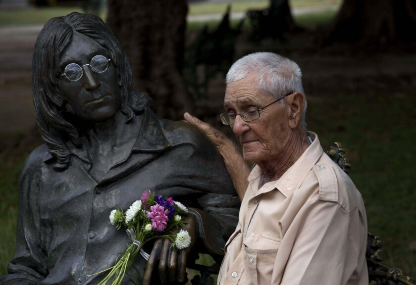Juan Gonzalez, poses next to the bronze statue of the late Beatle John Lennon in Havana, Cuba, Sunday, Dec. 8, 2013. When a statue of Lennon was inaugurated in a leafy Havana park 13 years ago, souvenir-seekers kept stealing the iconic circular spectacles that adorned it. When officials tried to glue them on, vandals simply broke them off. The solution: Gonzalez, the guardian of John Lennon's glasses, who has spent nearly all his days at the park for the last 13 years. He places the glasses gently on the crooner's nose when tourists show up to snap pictures, then tucks them away in his pocket when they leave. Despite his 96 years of age, Gonzalez says he's not ready to quit this one-man mission to help preserve the memory of one of music's all-time greats. Imagine. (AP Photo/Ramon Espinosa)