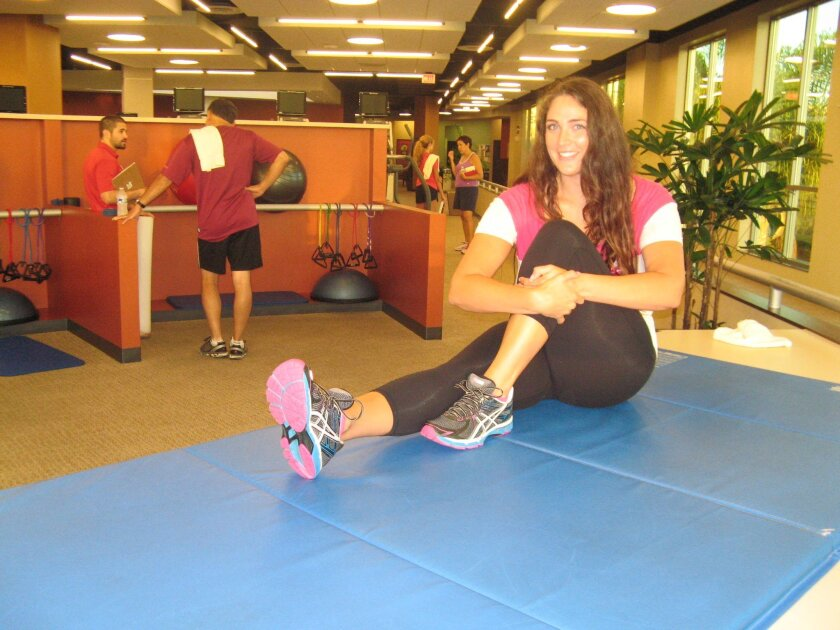 "Carlsbad resident Charlotte Dwyer stretches before running the indoor track at Tri-City Wellness in Carlsbad. Dwyer is among the ""Lucky 13"" chosen for free fitness training for an upcoming half marathon."