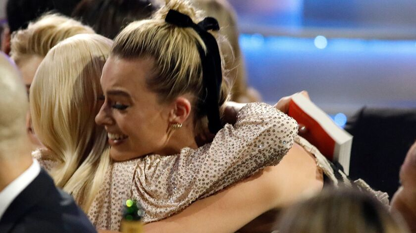 "Margot Robbie shares a hug with fellow nominee Saoirse Ronan after Robbie won the 2018 Critics' Choice Award for best actress in a comedy for her performance in, ""I, Tonya."""