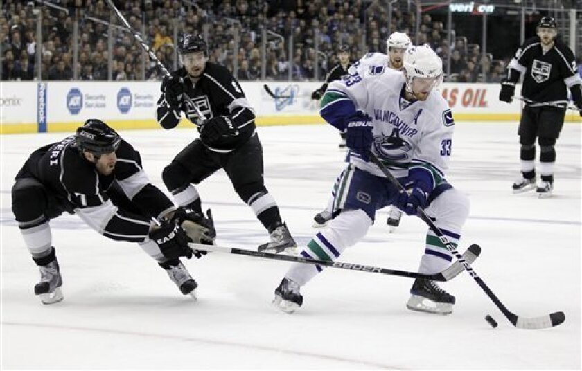 Los Angeles Kings defenseman Rob Scuderi, left, blocks a shot by Vancouver Canucks center Henrik Sedin, right, as defenseman Drew Doughty looks on during the first period in Game 6 of a first-round NHL hockey Western Conference playoff series in Los Angeles, Sunday, April 25, 2010. (AP Photo/Chris