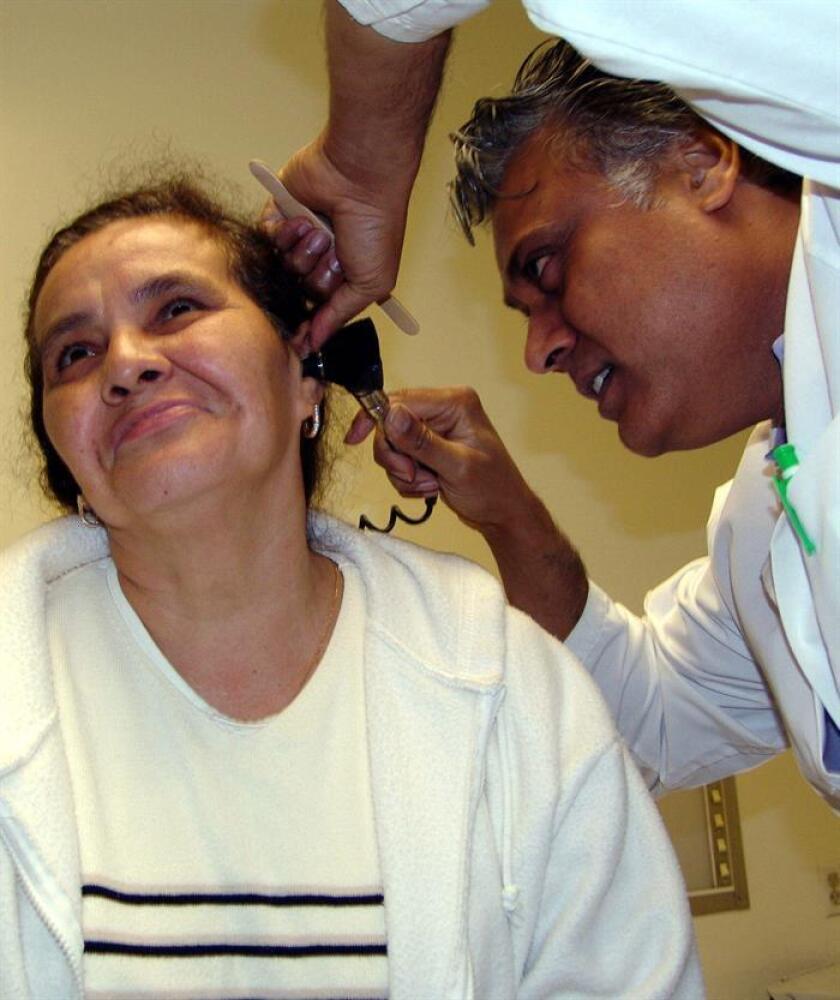 Vista de un médico que revisa el oído de una mujer. EFE/Archivo