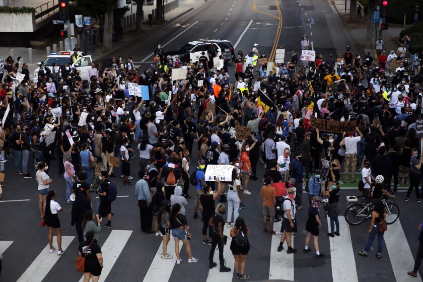 An overhead view of people standing in the middle of an intersection during a Black Lives Matter protest