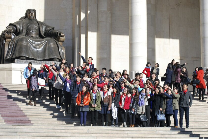 In this Friday, Oct. 30, 2015 photo, Mongolia schoolchildren pose for photos near the Chinggis Khaan statue in front of the Mongolian Parliament House in Ulaanbaatar, Mongolia. Sandwiched between China and Russia, landlocked Mongolia has long tread a middle path, maintaining a balance between Mosco