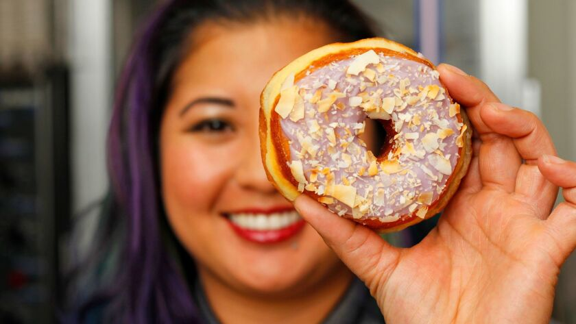 Pastry chef Kristianna Zabala with her top-selling ube taro coconut doughnut at Nomad Donuts in North Park.