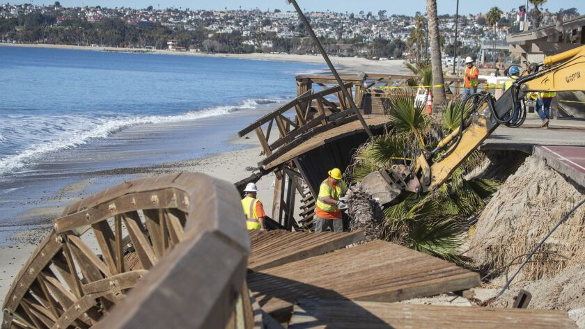 Orange County Public Works crews use heavy machinery to remove a boardwalk that was damaged in a recent storm at Capistrano Beach in Dana Point.