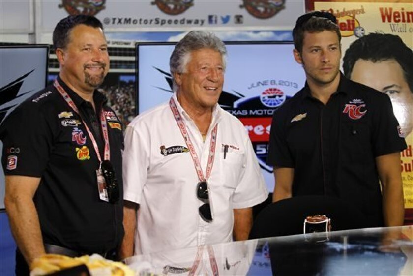 Michael Andretti, his father Mario and son Marco, right, pose for a group photo following a news conference at Texas Motor Speedway Friday, June 7, 2013, in Fort Worth, Texas. Marco is scheduled to race in Saturday's IndyCar Firestone 550 auto race. (AP Photo/Tim Sharp )